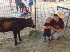 Malakai and Grandma with a baby cow.