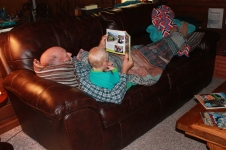 Grandpa reading a book to Malakai.